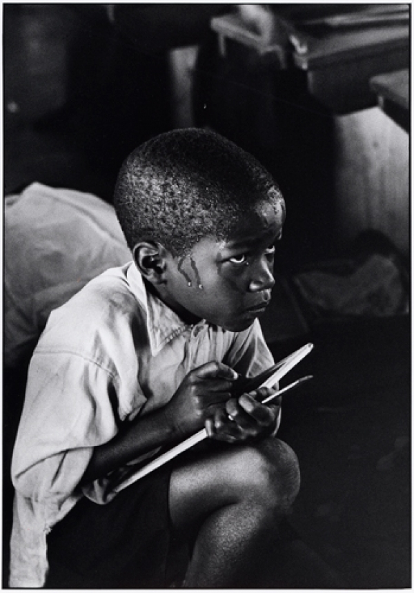 Earnest boy squats on haunches and strains to follow lesson in heat of packed classroom. 1967, Ernest Cole
